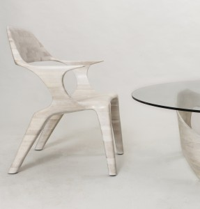 This is an image of a lounge chair made of bleached cherry, seen from the side, and the corner of a hand-sculpted coffee table