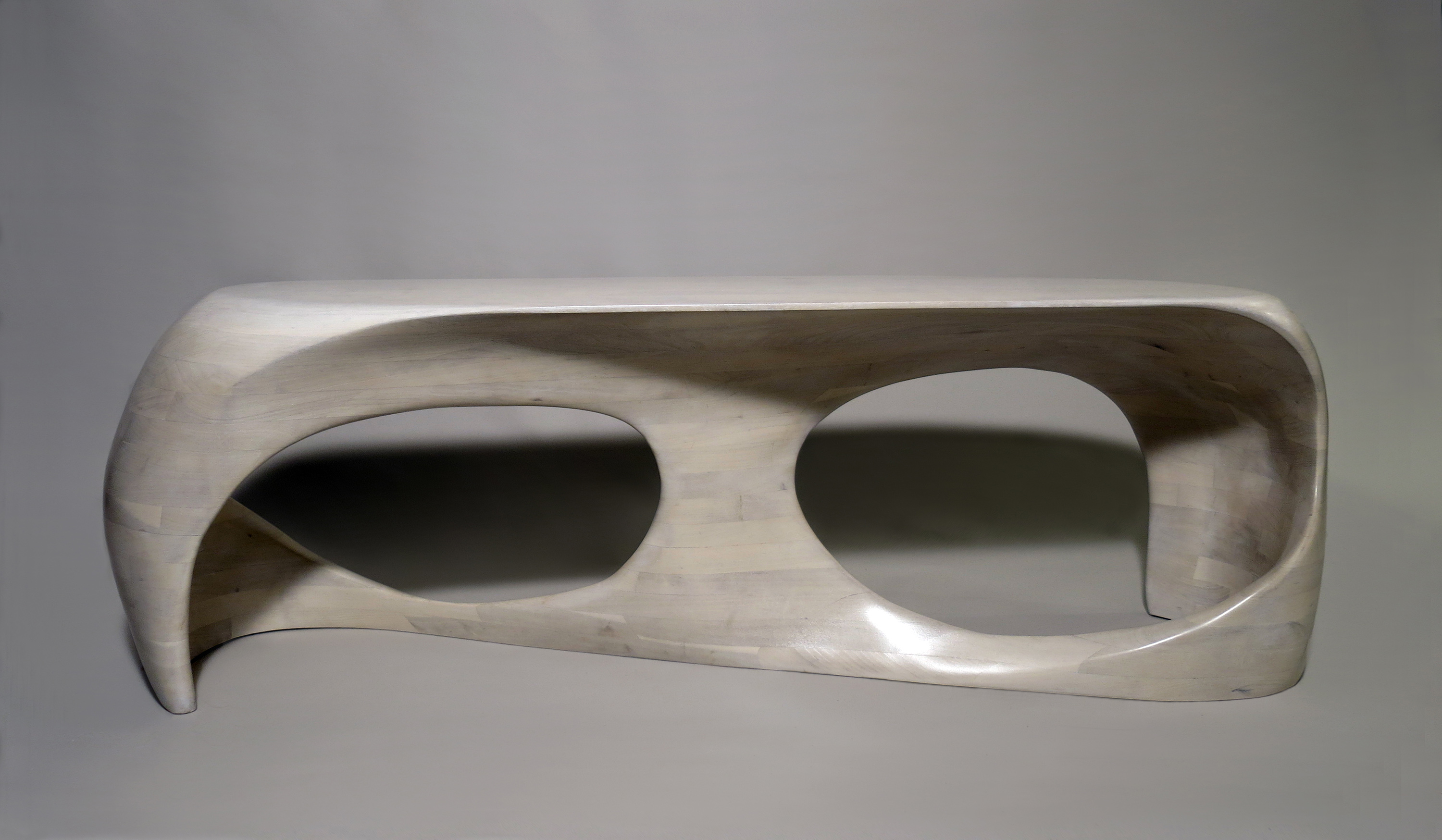 Photo of a hand-sculpted bench made of bleached cherry wood, seen from the front