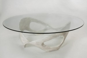 This photo shows an organic, sculpted wood coffee table base made of bleached cherry wood with a half-inch, circular glass top