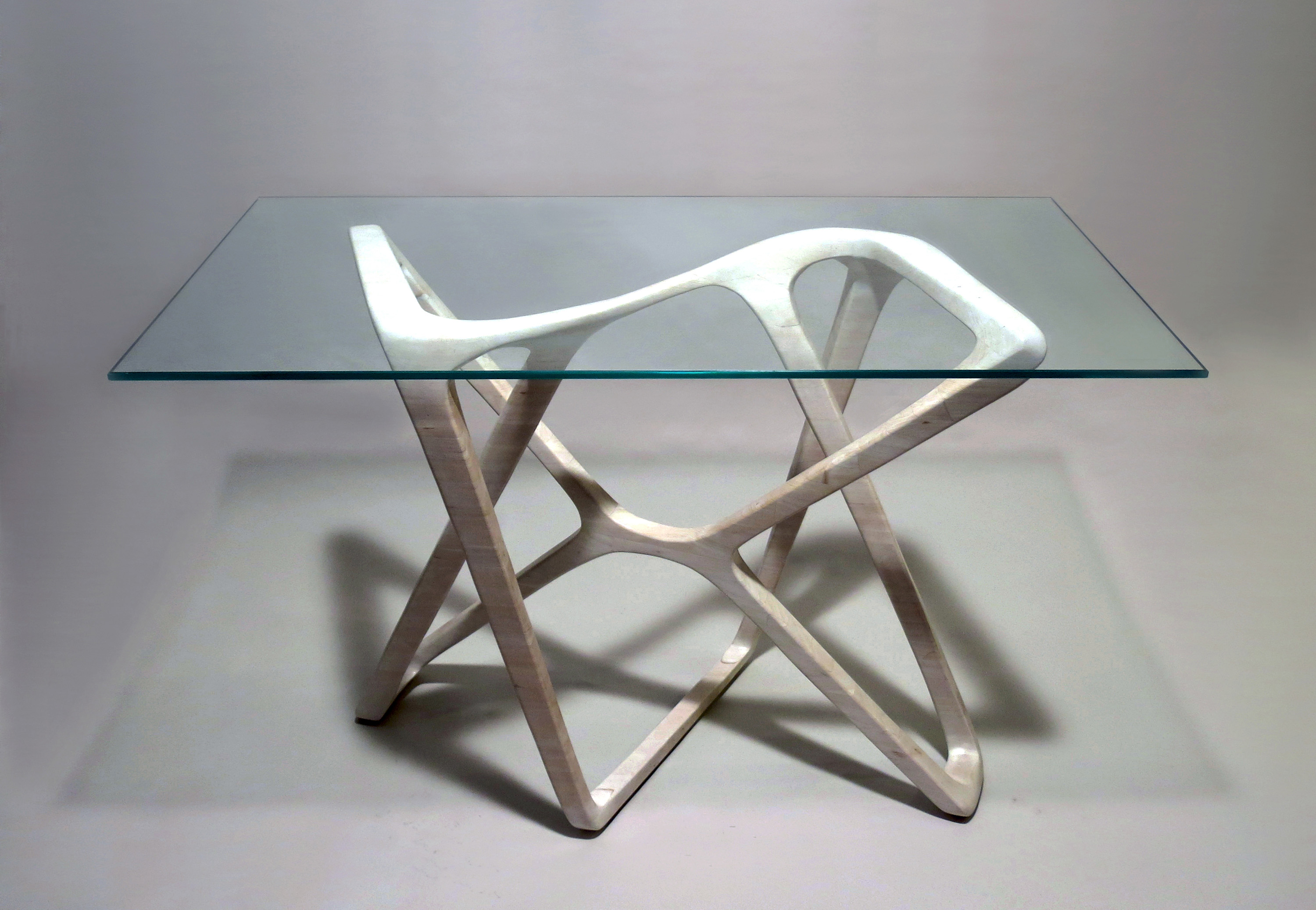 This image shows a rotationally-symmetrical wood desk base with a glass top