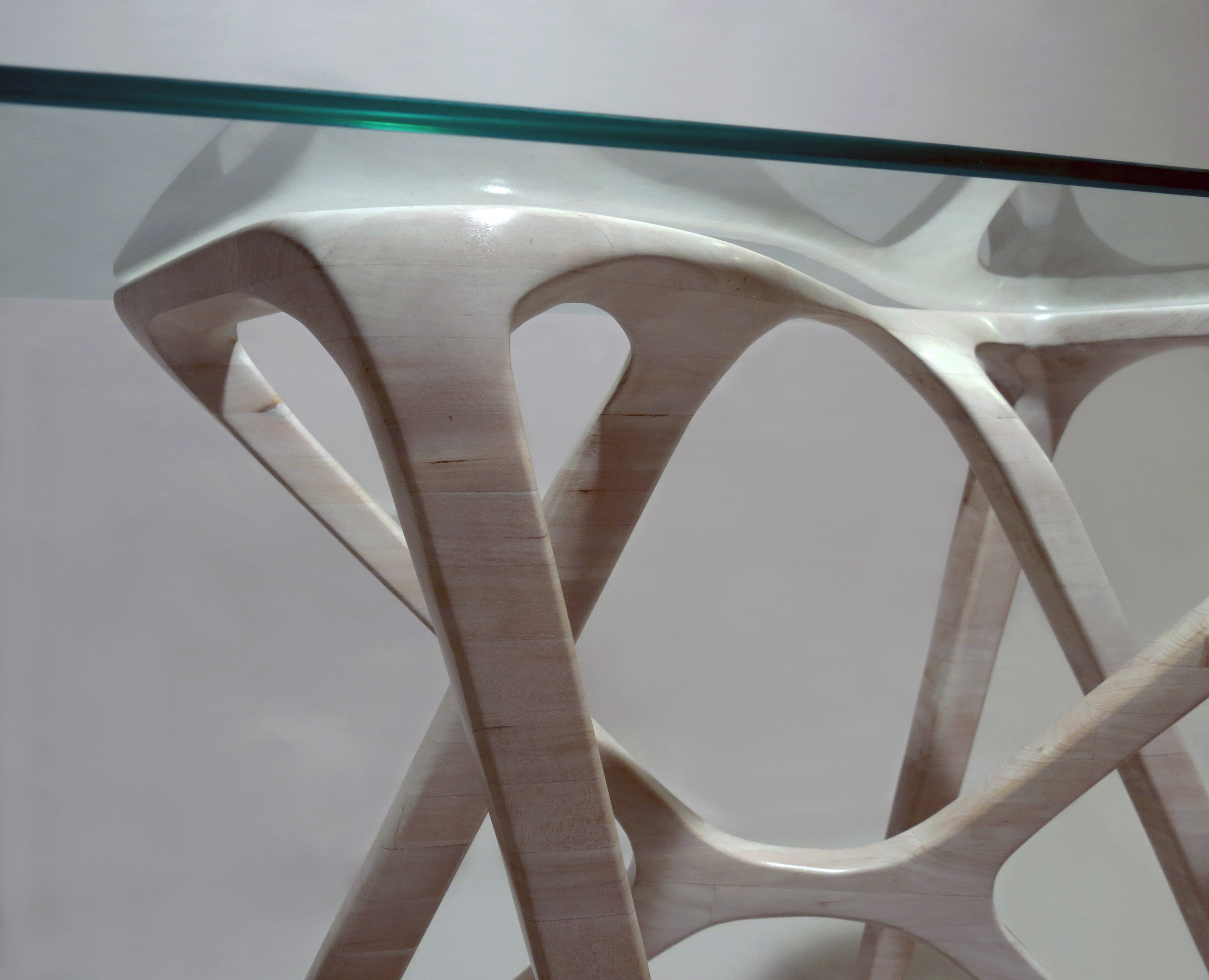 Photo of a detail from a sculpted wood desk base with a glass top