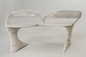 Photo of a bleached cherry loveseat sculpted by hand, seen from the front