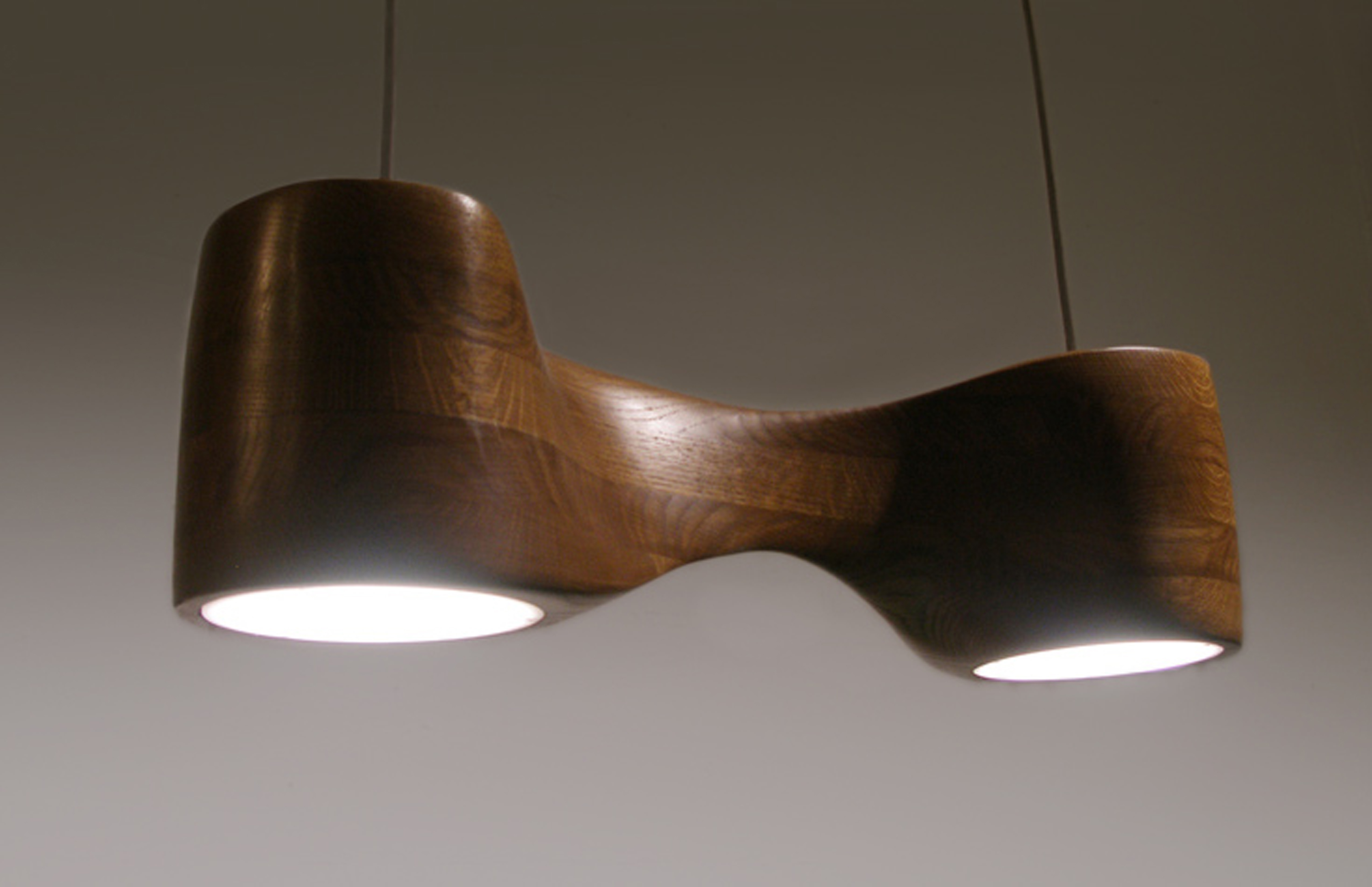 This is a photo of a sculpted pendant lamp in oak seen from three-quarters view