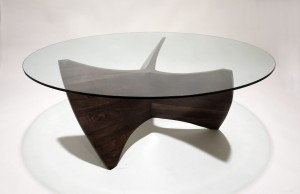 Photo of a propellor-like coffee table base made from walnut with a circular glass top