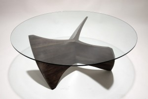 Coffee table base in walnut with a circular glass top seen from above