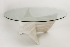 This photo shows a propellor-like dining table base made of bleached cherry wood with a sixty-four inch circular glass top