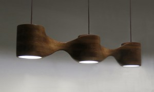This photo shows a pendant light with three lamps made from oak, seen from three-quarters view