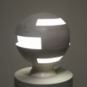This photo shows a spherical lamp made of wood with irregular cutouts for the light to pass through