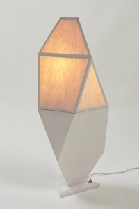 This photo shows a lamp made of geometric shapes covered with wood veneer, with the top half lit