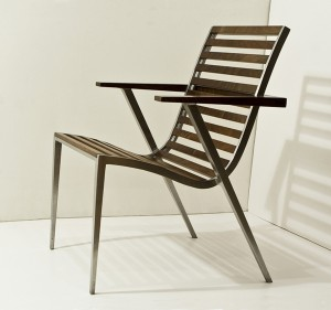 This is a photo of an aluminum and walnut dining chair seen from three-quarters view