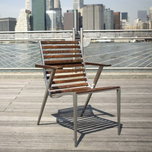 Dining chair made from cast aluminum and walnut shown on a promenade by the river