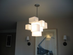 This is a photo of a cloud-like chandelier hanging in a living room, made from acrylic boxes, using an LED bulb